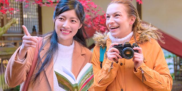 外国人旅行者を英語で手助けする女性